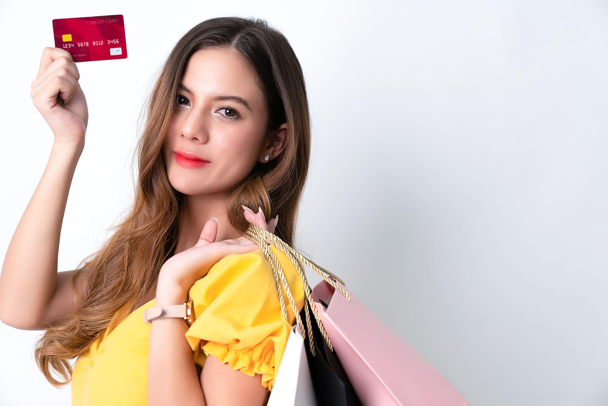ショッピングバックとクレジットカードを持つ女性